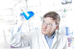 Germany, Young scientist checking blue liquid in erlenmeyer flask - stock photo