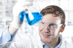 Germany, Young scientist checking blue liquid in erlenmeyer flask Stock Photos