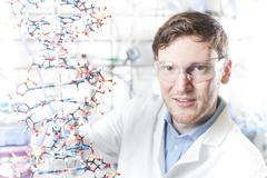 Germany, Portrait of young scientist with DNA model, smiling - stock photo