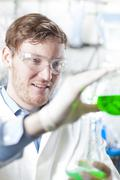 Germany, Young scientist pouring green liquid into erlenmeyer flask - stock photo