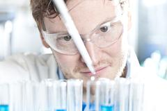 Germany, Young scientist pipetting blue liquid into test tubes, close up - stock photo