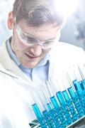Stock Photo of Germany, Young scientist pipetting blue liquid into test tubes, close up