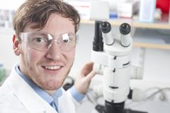 Stock Photo of Germany, Portrait of young scientist with microscope in laboratory, smiling