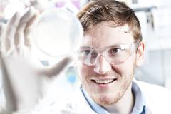 Germany, Young scientist checking petri desh, smiling - stock photo