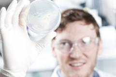 Stock Photo of Germany, Young scientist checking petri desh, smiling