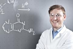 Germany, Portrait of young scientist standing next to chemical equation on chalk Stock Photos