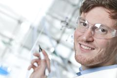 Stock Photo of Germany, Portrait of young scientist taking notes, smiling