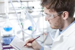 Stock Photo of Germany, Portrait of young scientist making notes in booklet, smiling