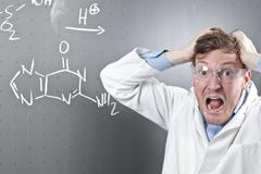 Germany, Young scientist with angry facial expression and chemical equation on - stock photo