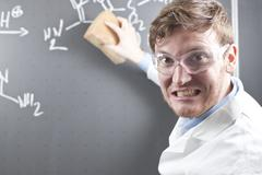 Germany, Young scientist erasing chemical equation on chalk board - stock photo