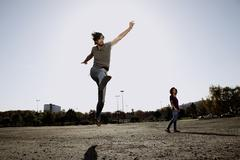 Stock Photo of Germany, Cologne, Man jumping in field, woman standing in background