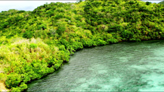 Stock Video Footage of Aerial along a tropical cove with lush forest covering the coastline