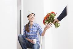 Human hand giving bunch of flowers to woman, smiling Stock Photos