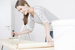 Woman applying glue on wallpaper - stock photo