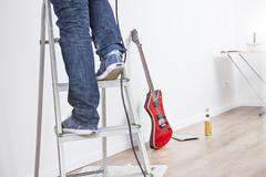 Stock Photo of Woman standing on step ladder, guitar and beer bottle in background