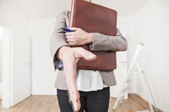 Woman with file and pen approaching for shake hand - stock photo