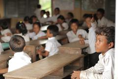 Cambodian Children - young boy looking out school  window - stock photo