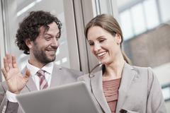 Germany, North Rhine Westphalia, Cologne, Businesscouple using laptop, smiling - stock photo