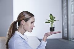 Stock Photo of Germany, North Rhine Westphalia, Cologne, Businesswoman lifting potted plant,