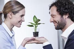 Stock Photo of Germany, North Rhine Westphalia, Cologne, Businesscouple holding potted plant,