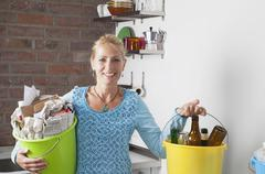 Germany, Cologne, Mature woman carrying buckets with household garbage in - stock photo