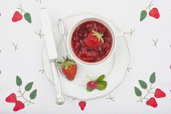 Bowl of fresh homemade strawberry jam on plate Stock Photos