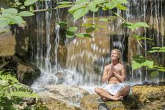 Austria, Altenmarkt-Zauchensee, Mid adult woman meditating near waterfall - stock photo