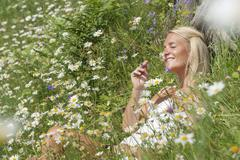 Austria, Salzburg, Mid adult woman with flowers in meadow, smiling Stock Photos