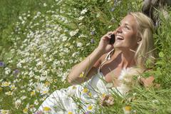 Stock Photo of Austria, Salzburg, Mid adult woman talking on cell phone in meadow, smiling
