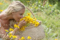 Stock Photo of Austria, Altenmarkt-Zauchensee, Mid adult woman in alpine meadow with arnica