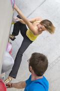 Germany, Bavaria, Munich, Young man helping woman to climb - stock photo