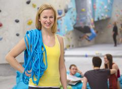 Germany, Bavaria, Munich, Woman with climbing rope while friends relaxing in - stock photo