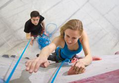 Germany, Bavaria, Munich, Young woman bouldering while man holding rope Stock Photos
