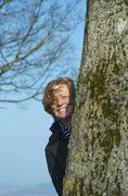 Germany, Baden Wuerttemberg, Constance, Mature woman hidding behind tree, Stock Photos