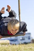 Stock Photo of Germany, Kiel, Girl on swing, smiling