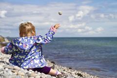 Denmark, Girl sitting on beach, throwing stone in ocean - stock photo