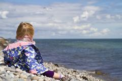 Denmark, Girl sitting on beach and looking over blue water Stock Photos