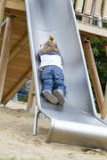 Germany, Girl playing on slide Stock Photos