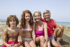 Spain, Grandparents with grandchildren sitting at beach, smiling, portrait Stock Photos