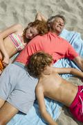 Spain, Grandfather and grandchildren relaxing on beach Stock Photos