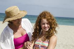 Spain, Grandmother and granddaughter at beach, smiling - stock photo