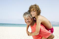 Spain, Grandfather giving piggyback ride to grandson, smiling - stock photo