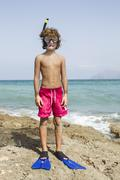 Spain, Boy with diving equipment on beach - stock photo
