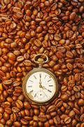 Germany, Coffeebeans with antique clock, close up Stock Photos