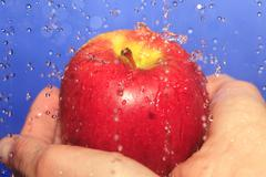 Human hand holding apple with waterdrops, close up - stock photo