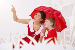 Stock Photo of Mother and daughter under umbrella, smiling
