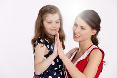 Mother and daughter comparing their hands, smiling Stock Photos