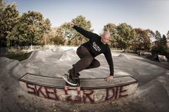 Stock Photo of Germany, North Rhine Westphalia, Duesseldorf, Mature man jumping with skateboard
