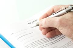 Stock Photo of Human hand signing authority document, close up