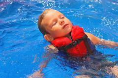 Stock Photo of tranquil kid in vest floating on her back at the pool aqua park